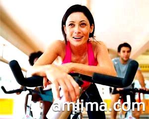 Дівчина крутить педалі в фітнес-центрі
