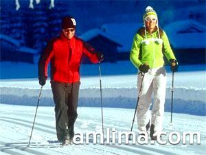Сімейна пара взимку займається скандинавської ходьбою