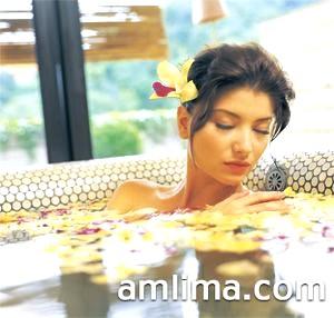 Дівчина лежить у ванні з пелюстками троянд